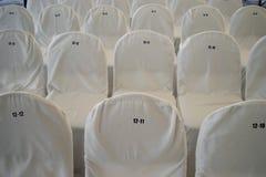 Stolar som är dolda med vita överkast med nummer Arkivbild