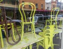 Stolar som staplas upp i ett restaurangfönster Arkivbild