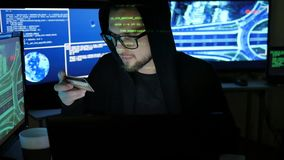 Stolen bank card hacker holds in hands, cyber criminal, steal finances through the internet, male hacker cracking