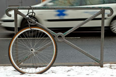 Stolen bicycle. Bicycle wheel locked alone to a gate. In the background, an ambulance Stock Photo