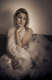 Stolen dreams. Blond sad woman wrapped in white veil royalty free stock photo