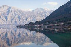 Stoliv和反射地中海村庄与山的在水中在一个冬日 亚得里亚海,黑山科托尔海湾  免版税库存照片