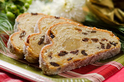 Stollen Fruit Cake. Close up of sliced stolen fruit cake against a festive colourful background Royalty Free Stock Image