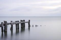 Stolpar av en bruten pir som leder ut in i stillsamt hav w för stillhetblått arkivfoto