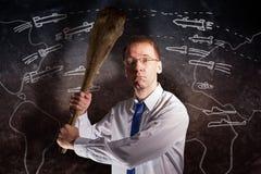 Stolpe-apokalyps En modern man med en pinne i hans händer hotar mot bakgrunden av en vagga med teckningar av missiler royaltyfria foton