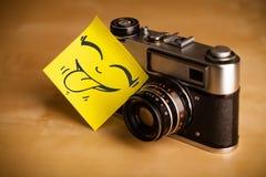Stolpe-det noterar med smileyframsidan sticked på fotokamera Arkivfoto