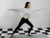 Stolpe för härlig asiatisk instruktör-, undervisayoga för flicka på skum, med den vita tegelstenväggen som en bakgrund, öv arkivfoton