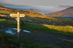Stolpe för UK-vandringsledfinger som fångar solen Arkivbild