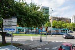Stolpe för universitetsområdeNord tecken med den rörande spårvagnen bakom i Barcelona arkivbilder