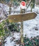 Stolpen för tecknet för riktningen för julvintertid täckte den tomma med ingen text på den i ett lager av snö och med en Santa Cl royaltyfri fotografi