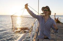 Stolt attraktiv fiskarevisningfisk och tillfångataganden för krabbakorg som netto ler på havsskeppsdockasolnedgången i manfiske s arkivfoto