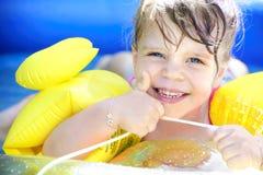 Stolt liten flicka i simbassängen royaltyfri foto