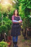 Stolt ungt barnkammareägareanseende i ett växthus Royaltyfri Foto