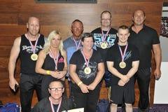 Stolta manliga och kvinnliga konkurrenter som visar deras medaljer och trofé Royaltyfria Foton