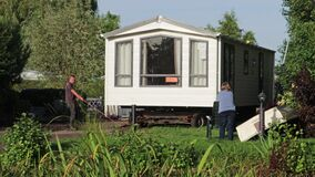 Static caravan being manoeuvred on a caravan site on a trailer. Worker pulling on rope to steer with tractor pushing