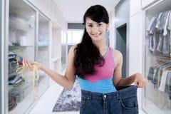 Stolze asiatische Frau, die ihr Gewichtsverlust zeigt Stockbild