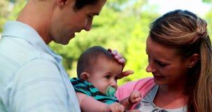 Stolze Eltern, die Babysohn im Park halten stock footage