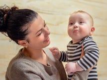 Stolze junge Mutter mit ihrem Babysohn Stockfoto