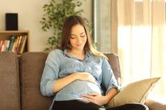 Stolze schwangere Frau, die ihren Bauch schaut Lizenzfreies Stockfoto