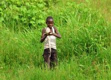 Stolzer afrikanischer Junge fängt Fische, um Familie einzuziehen Lizenzfreie Stockfotografie