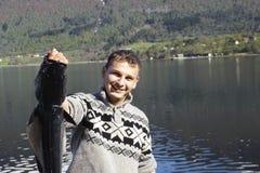 Stolzer Fischer, der einen großen Fisch anzeigt Lizenzfreies Stockfoto