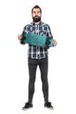 Stolzer Hippie, der das lange Brett betrachtet Kamera hält Lizenzfreie Stockfotografie