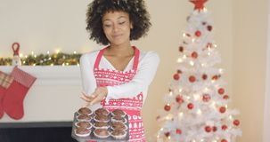 Stolzer Jungekoch, der ihre Weihnachtsmuffins anzeigt Stockfoto