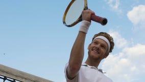 Stolzer männlicher Tennisspieler nahe dem Netz, das erfolgreiches Ergebnis, Führung zeigt stock video footage