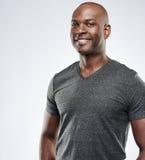 Stolzer muskulöser afrikanischer Mann mit angenehmem Lächeln Stockfotos