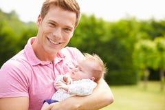 Stolzer Vater Holding Baby Daughter im Garten Lizenzfreies Stockbild