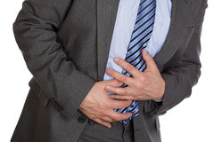 Stomach ache. Businessman holding his stomach in pain or indigestion