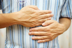 Stomach ache, man placing hands on the stomach, concept of sto Stock Photography