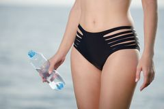 Stomach beautiful and sporty body of sexy woman in bikini with bottle of water in hand.  Royalty Free Stock Photography