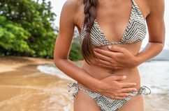 Stomach bug travel disease woman tourist with painful cramps on tropical beach - norovirus gastroenteritis concept. Cramp pain. Health insurance royalty free stock image