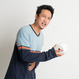 Stomach pain and running to toilet. Asian male stomach pain holding toilet paper running to toilet, with painful face expression, on plain background Royalty Free Stock Images