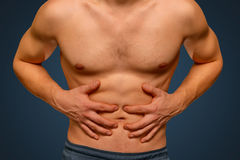 Stomach pain. Unrecognizable man compresses the abdomen due to pain Royalty Free Stock Photo