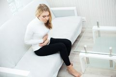 Stomach pain. Woman having painful stomachache,Female suffering from abdominal pain stock photography