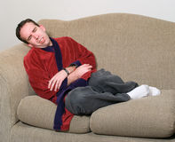 Stomach Pains. Young man clenching because he is feeling stomach pains from being sick Royalty Free Stock Image