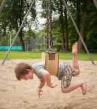Stomach swinging. A young boy swinging on the swingset on his belly with his legs and arms flaying royalty free stock images