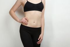 Stomach of thin, sports girl. The stomach of thin, sports girl on grey background Royalty Free Stock Photos