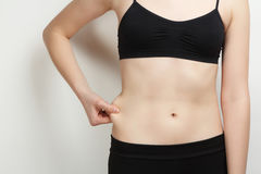 Stomach of thin, sports girl. The stomach of thin, sports girl on grey background Stock Photo
