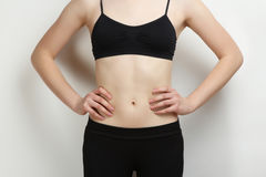 Stomach of thin, sports girl. The stomach of thin, sports girl on grey background Stock Photos