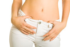 Stomach of woman in white jeans Royalty Free Stock Photography