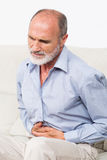 Stomachache. Businessman sitting and suffering from stomachache Stock Photography