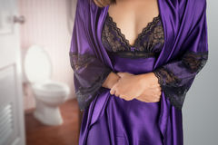 Stomachache. The woman in  purple satin sleepwear and robe wake up for go to restroom. People with diarrhea problem concept Royalty Free Stock Photos