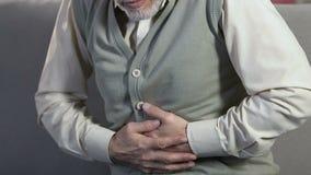 Stomaco anziano della tenuta dell'uomo, dolore acuto ritenente, soffrente dai problemi sanitari video d archivio