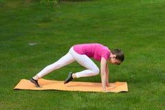 Stomaco dai capelli di addestramento della donna di Brown, parte posteriore, armi e muscoli delle gambe in plancia sulla stuoia Fotografie Stock