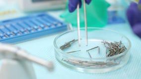 Stomatolog ręka w lateksowych rękawiczkach trzyma medyczne pincety Stomatologiczni świderów rzepy zbiory wideo