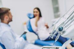 Stomatologiczni narzędzia z lekarką opowiada z pacjentem fotografia royalty free