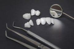 Stomatologiczni narzędzia i zircon dentures na ciemnym tle lumineers - Ceramiczni forniry - Zdjęcia Royalty Free